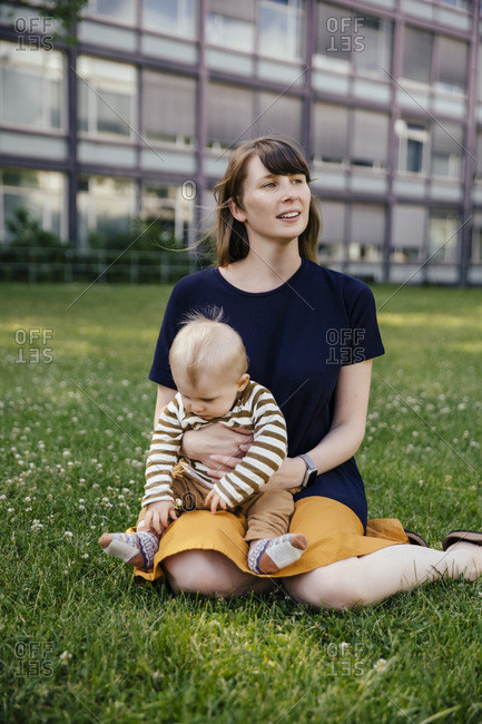 Mother sitting with her baby boy on a meadow