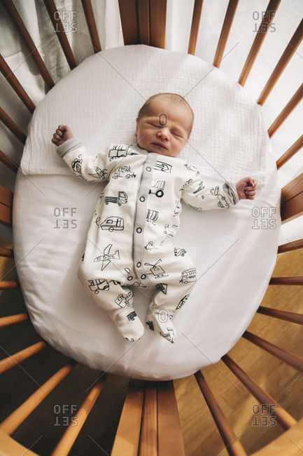 One-day-old baby boy lying in his crib at home