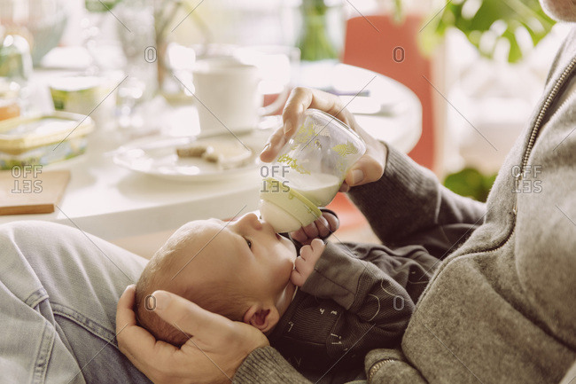 Father bottle-feeding his newborn baby boy
