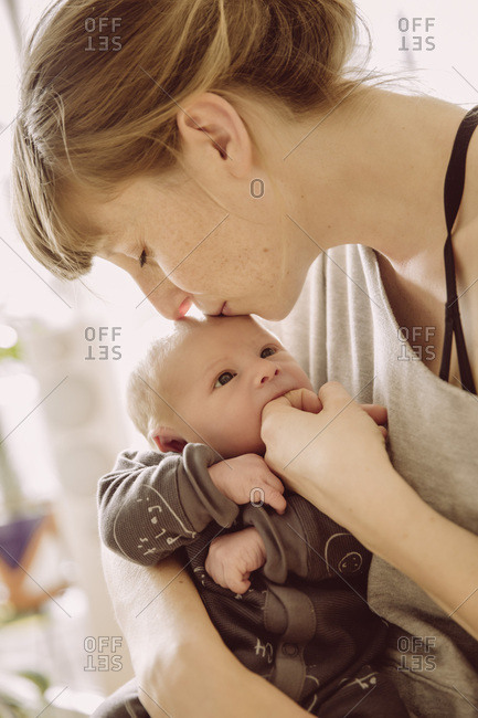 Mother testing newborn baby's hunger with her finger and kissing its forehead