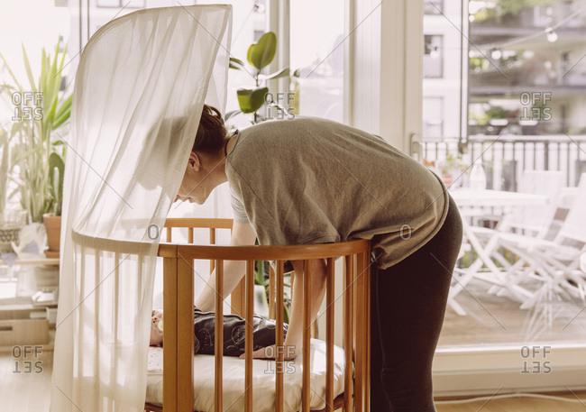 Mother laying her newborn baby boy into crib