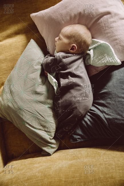 Newborn baby lying and napping on couch between pillows