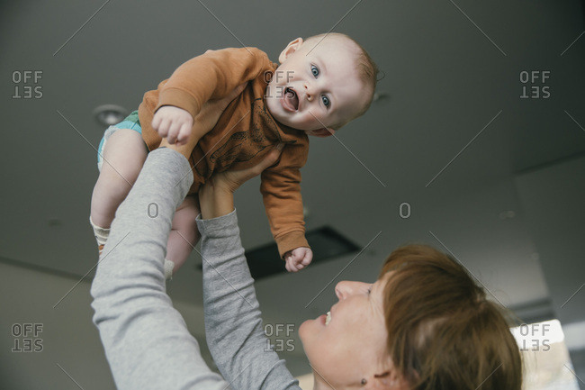 Grandmother lifting up baby at home
