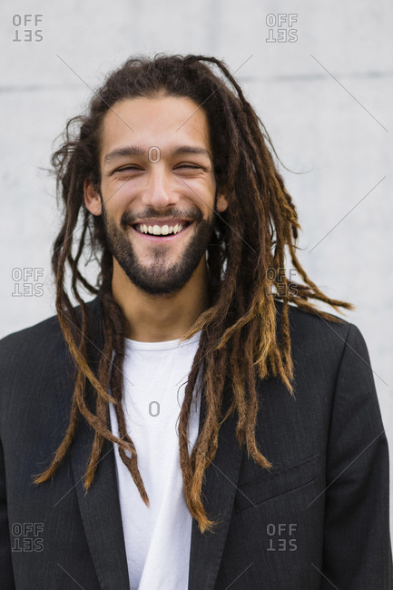 Portrait of smiling young businessman with dreadlocks