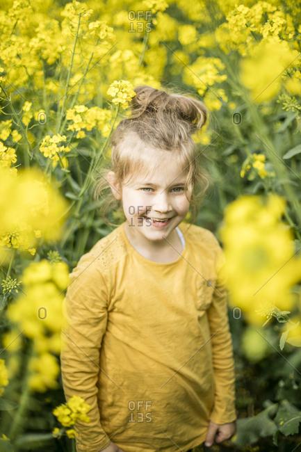 Happy girl standing in rape field