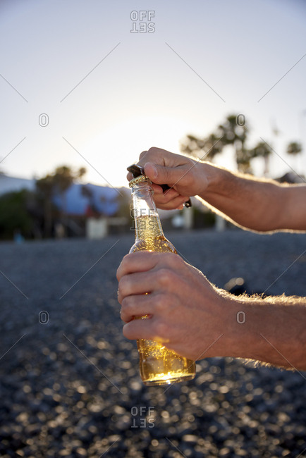 Man's hands opening beer bottle on the beach