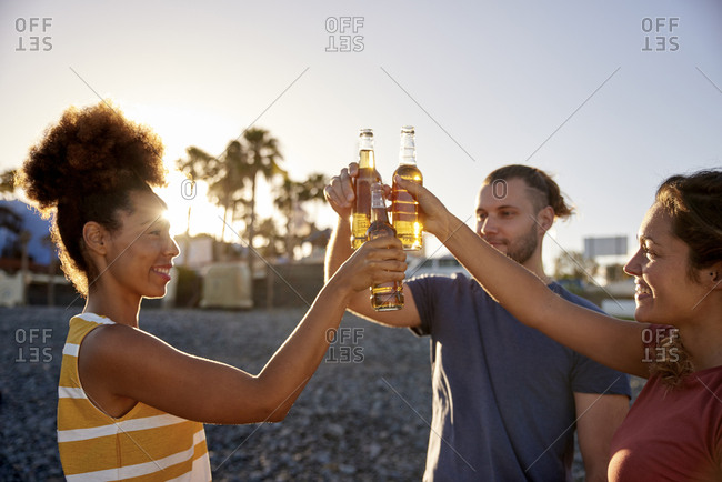 Three friends toasting with beer bottles on the beach