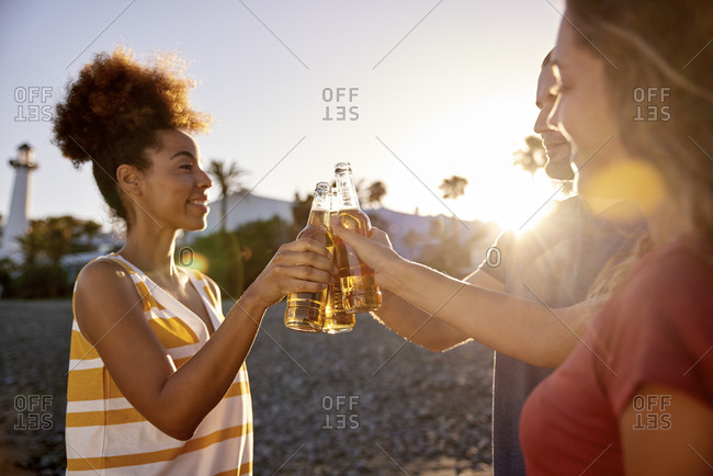 Three friends toasting with beer bottles on the beach at sunset