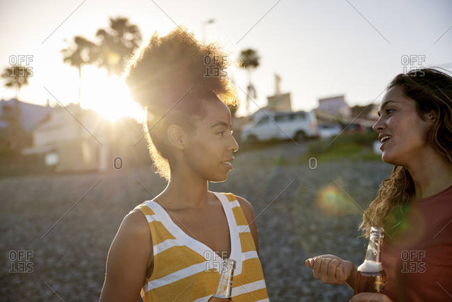 Two friends talking on the beach at sunset