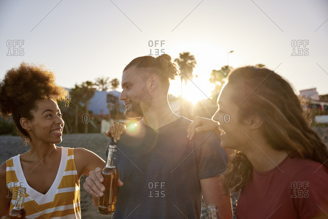 Three friends with beer bottles on the beach at sunset