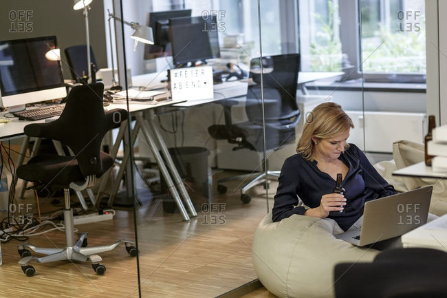 Businesswoman with beer bottle and laptop in office