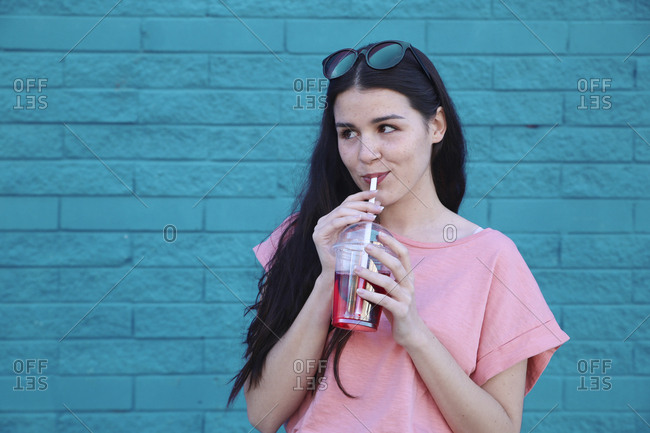 Portrait of young woman drinking soft drink