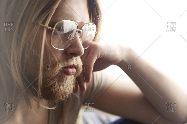 Portrait of pensive young man with long blond hair wearing spectacles