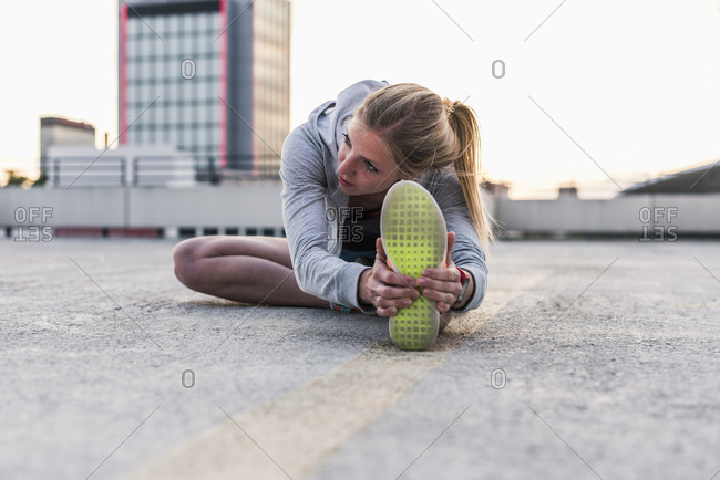 Active woman stretching on parking level in the city