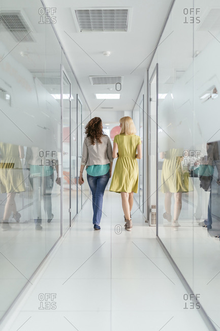 Two female colleagues walking in office corridor