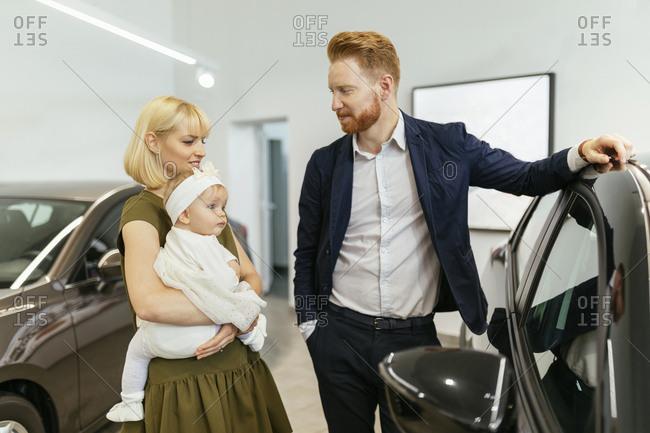 Family in car dealership choosing family vehicle
