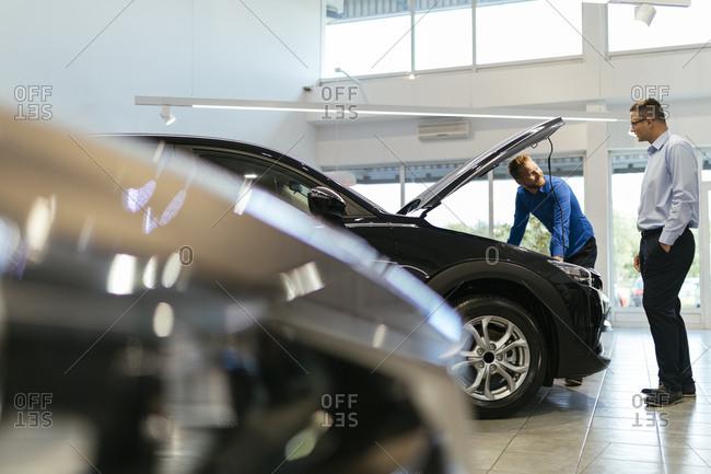 Salesman advising customer in car dealership