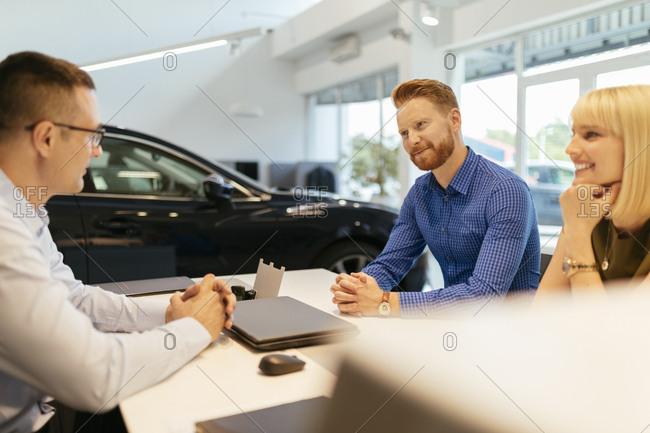 Salesperson advising couple in car dealership