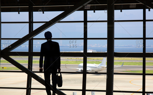 Silhouette of man viewing airplane out airport window