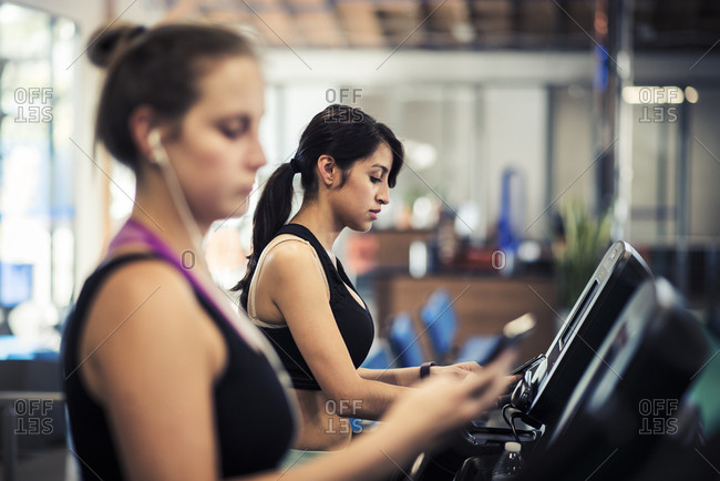 Young woman with female friend exercising on treadmills in gym