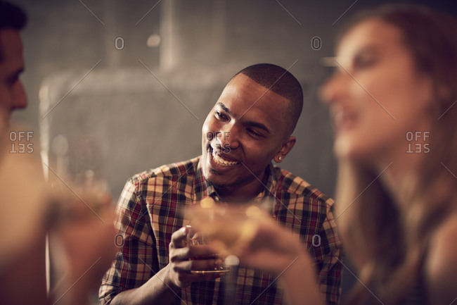 Happy young man having drink while sitting with friend in bar