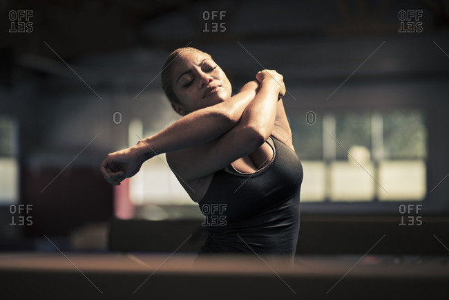 Mid adult female gymnast stretching her arms in gym