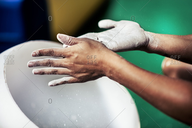 Cropped image of female athlete coating her hands in powder chalk magnesium at gym