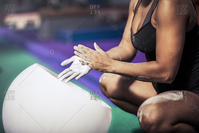 Midsection of female athlete coating her hands in powder chalk magnesium at gym