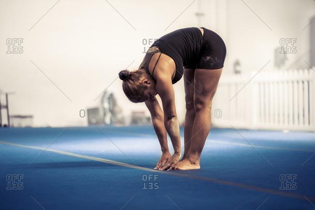 Sporty female stretching at gym