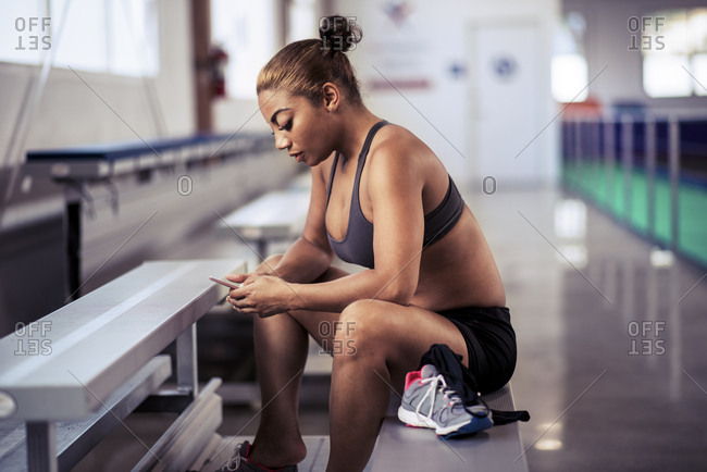 Sporty mid adult female athlete using mobile phone while sitting on bench at gym