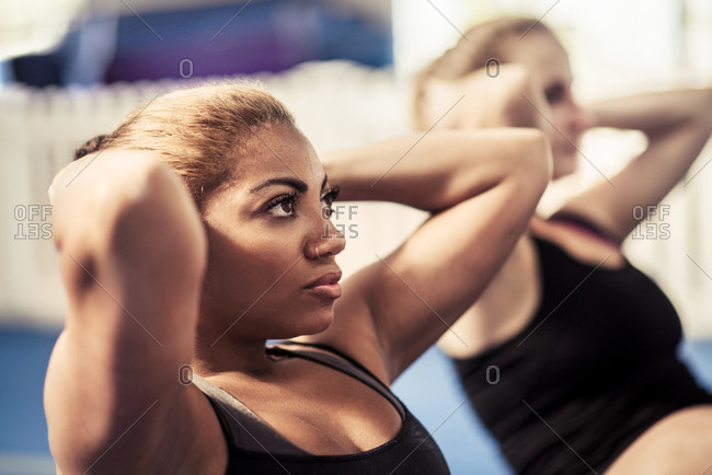 Sporty female athlete with friend doing crunches  at gym