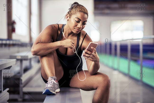 Confident female athlete listening music with earphones and smartphone at gym