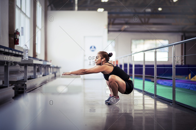 Full length side view of determined female athlete doing squats at gym