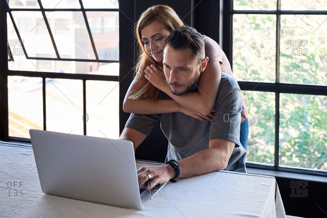 Attractive woman hugs boyfriend from back as he concentrates on work typing on laptop computer working from home