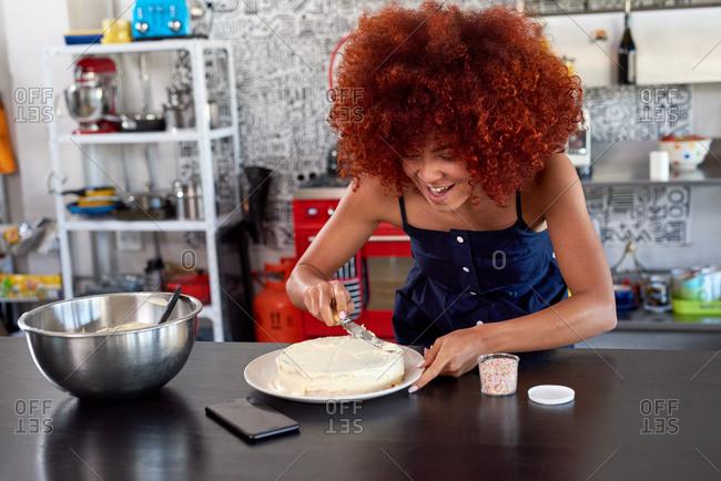 Home baker frosting her homemade cake in open plan modern kitchen, passionate hobby baking