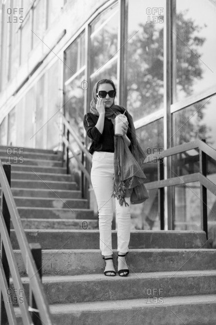 Young woman standing on outdoor steps talking on a cellphone