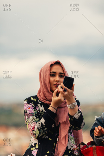 Young woman using a makeup compact to apply lipstick