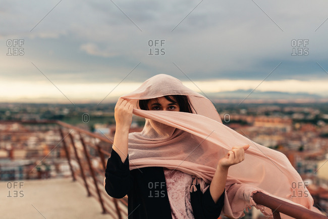 Young woman standing on a balcony with a scarf covering her face