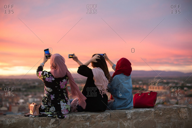 Friends sitting on a wall overlooking a city taking photos
