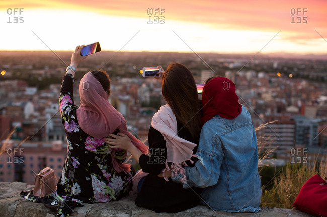 Three friends sitting on a wall taking photos of a sunset