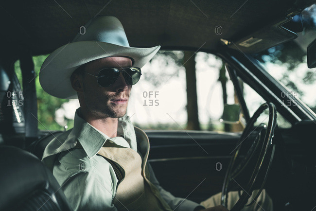 Man in a cowboy hat and sunglasses sitting in a retro car