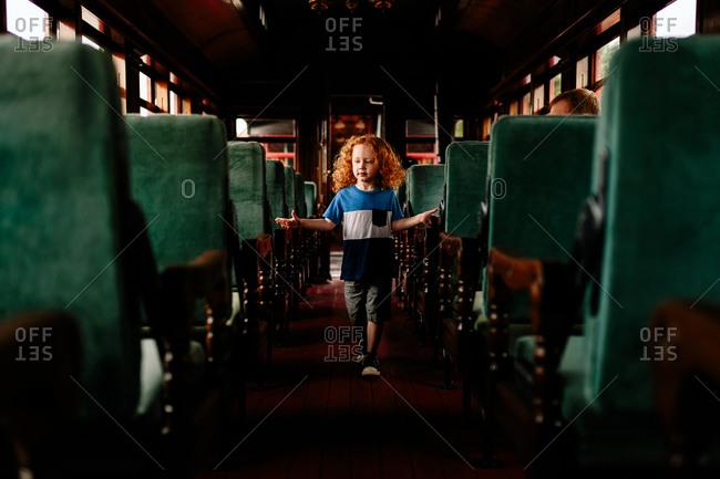 Child walking through antique passenger car on train
