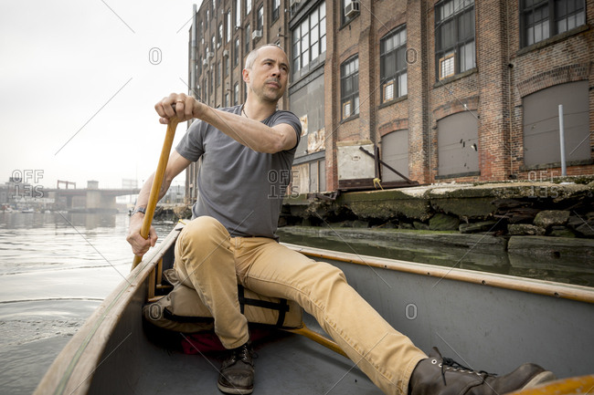 A man exploring and canoeing up a river in Brooklyn, New York.