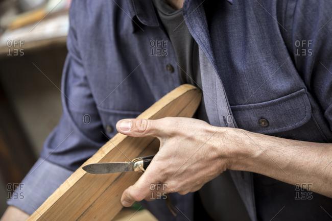 A man carving a wood oar in a workshop.