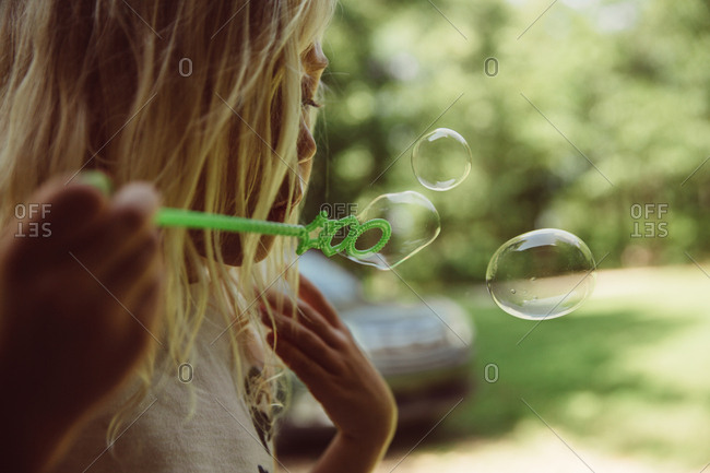 A girl blowing bubbles in close up
