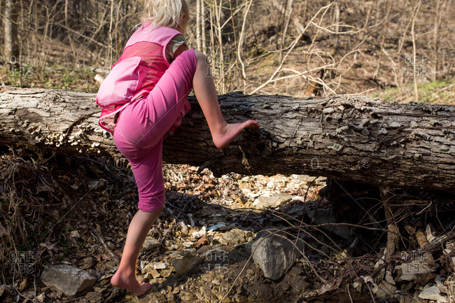 Girl climbing log in woods in early spring