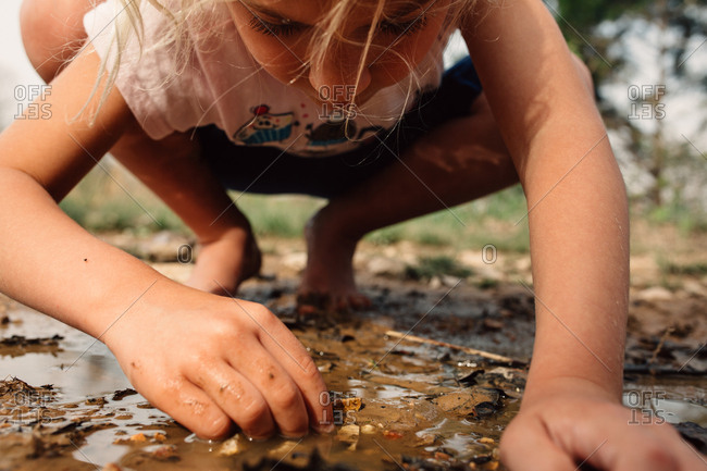 Close up of girl exploring dirt and mud