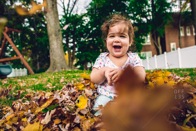 Baby girl playing in autumn leaves