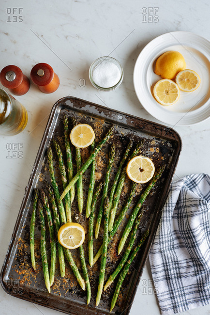 Baked Asparagus laid out on a sheet with melted parmesan cheese melted on top, with lemons nearby.