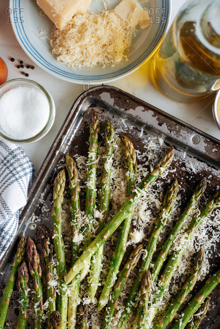 Asparagus spears laid out on a baking sheet, with grated parmesan cheese and olive oil, salt and pepper nearby.